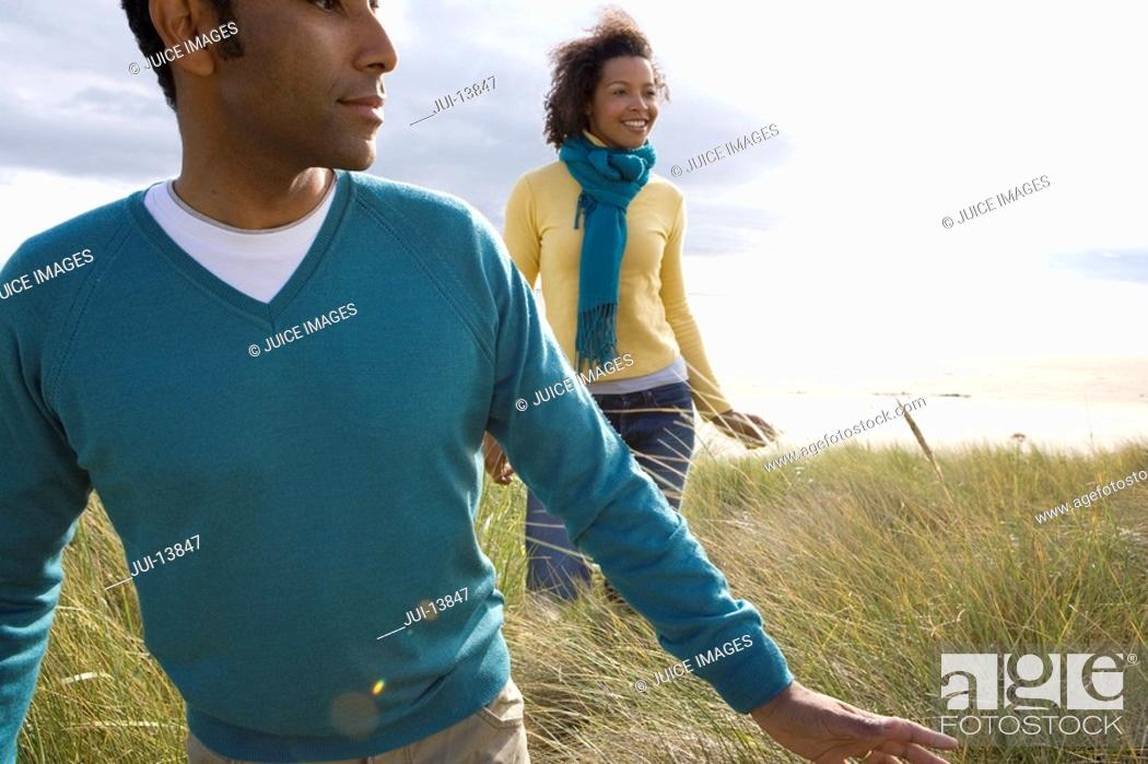Stock Photo: Young couple on sand dunes, smiling.