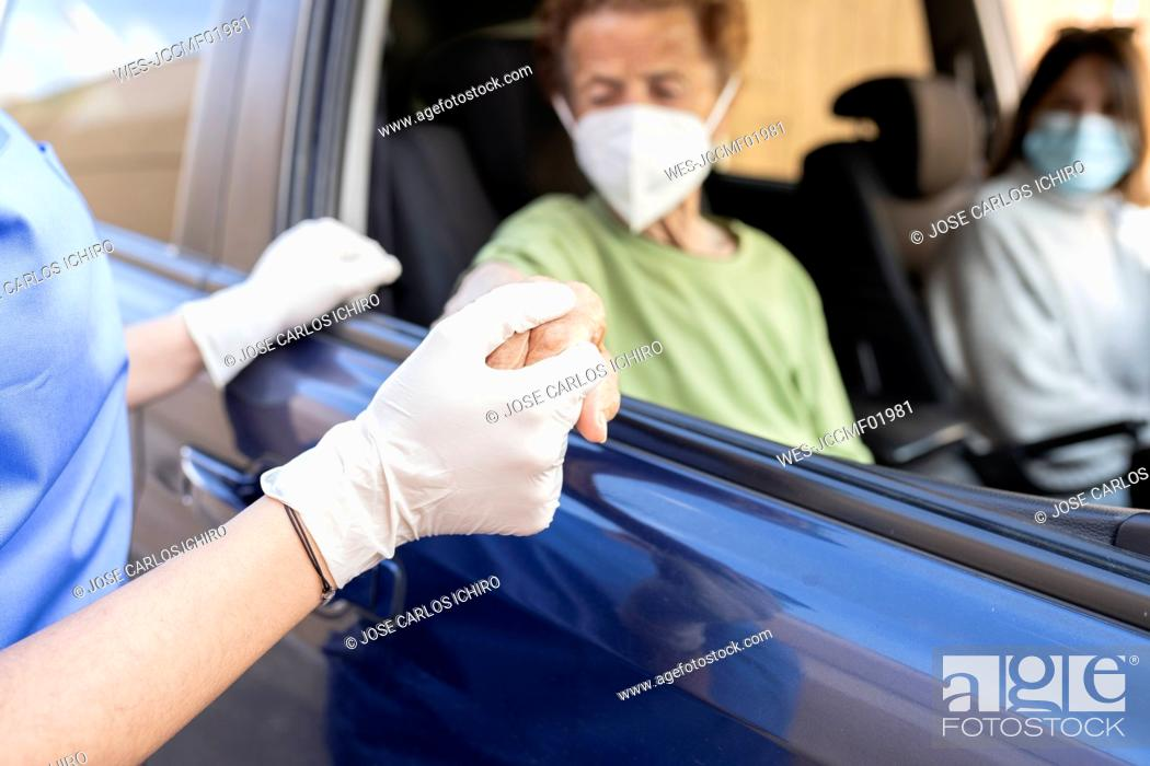 Imagen: Female healthcare worker holding hand of senior patient sitting in car.