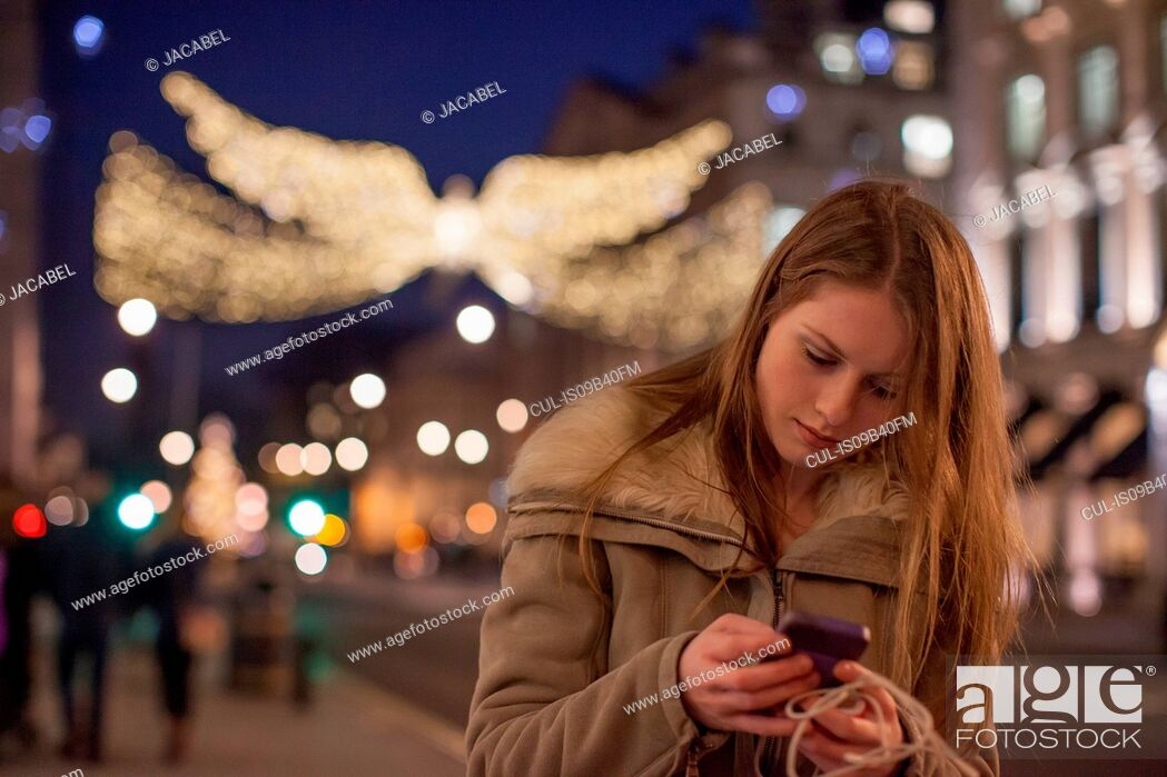 Stock Photo: Young woman using mobile phone in street, London, UK.