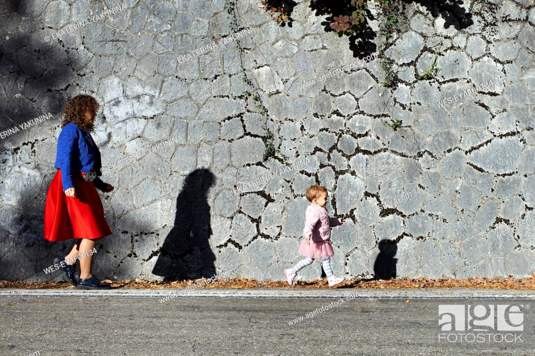 Stock Photo: Little girl running with her mother at a stone wall.
