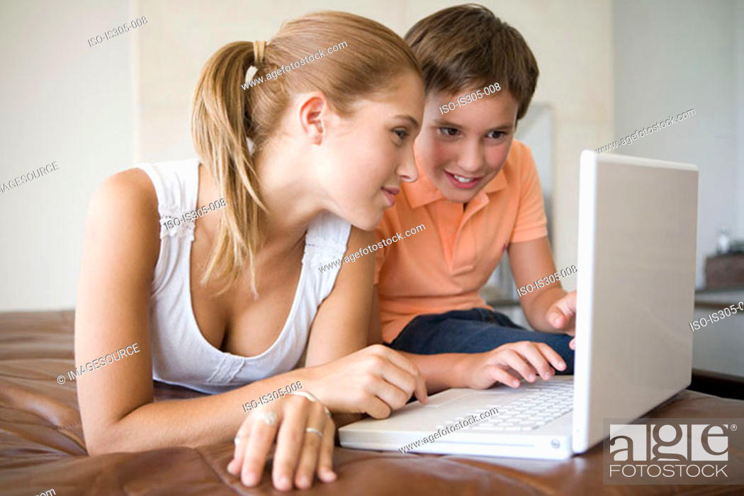 Stock Photo: Brother and sister using laptop.