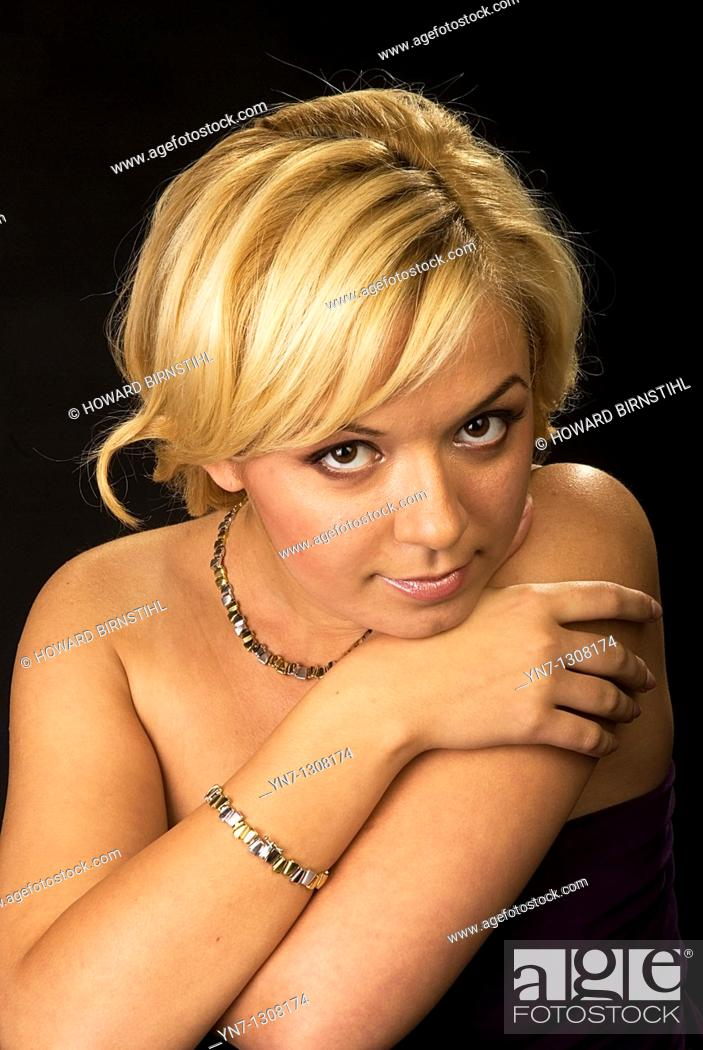 Stock Photo: young blond model leaning chin on hand and smiling at the camera ideal for jewellery overlays.