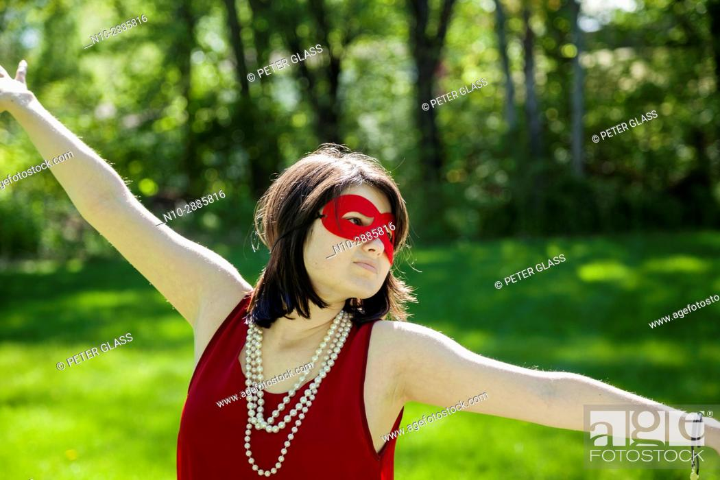 Stock Photo: Young woman, with arms outstretched, wearing a mask, pearl necklace, and red dress in a park.
