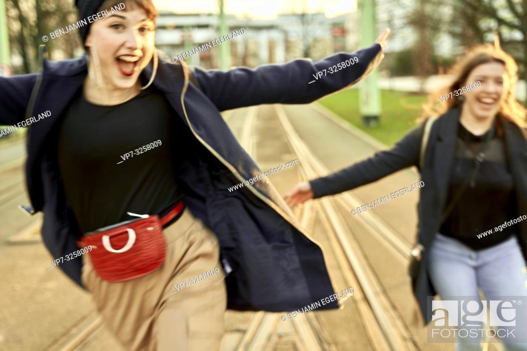 Imagen: two adventurous women running at street in city Cottbus, Brandenburg, Germany.