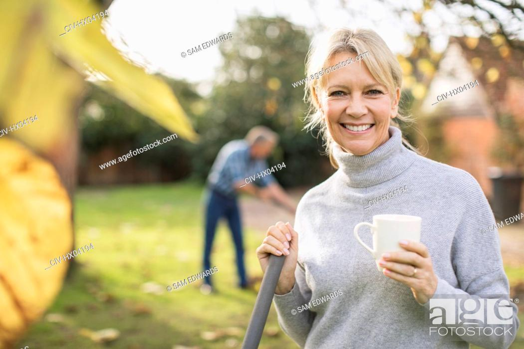 Stock Photo: Portrait smiling, confident mature woman drinking coffee and raking autumn leaves in backyard.