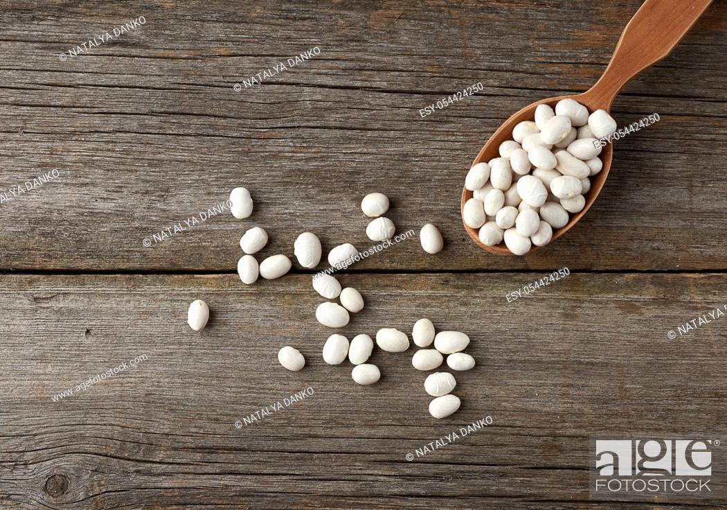 Stock Photo: white raw whole beans in a brown wooden spoon on the table, top view.