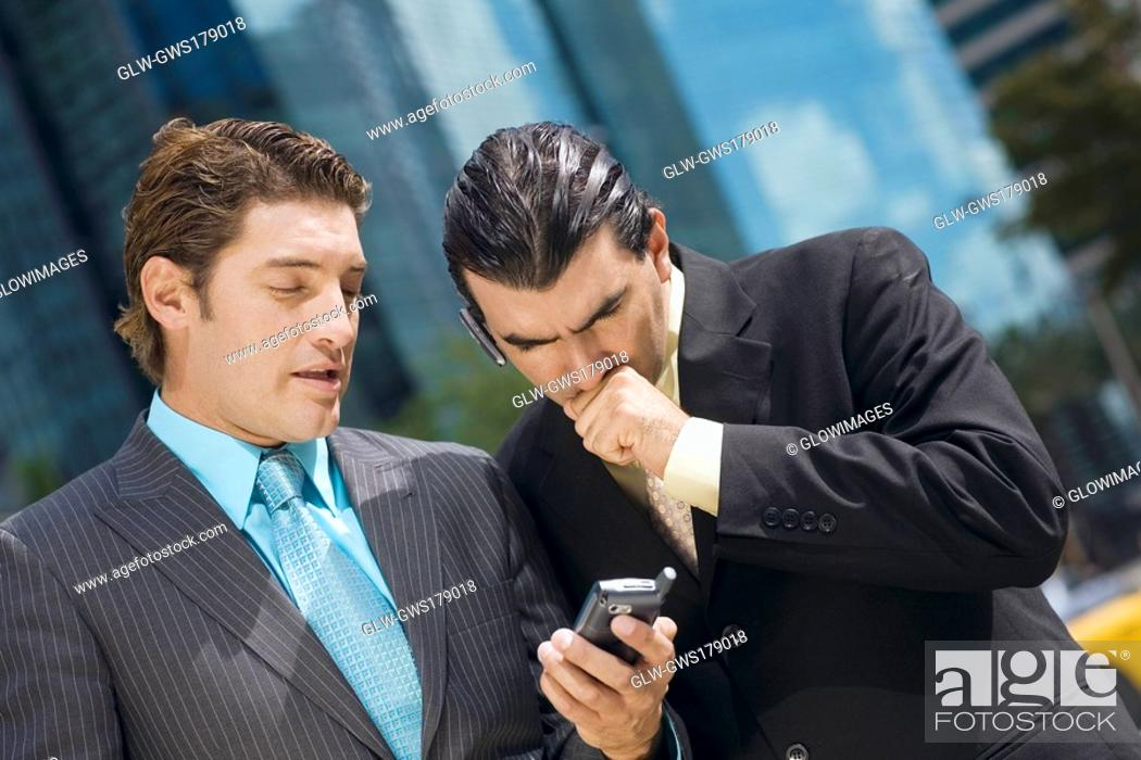 Stock Photo: Two businessmen looking at a hand held device.