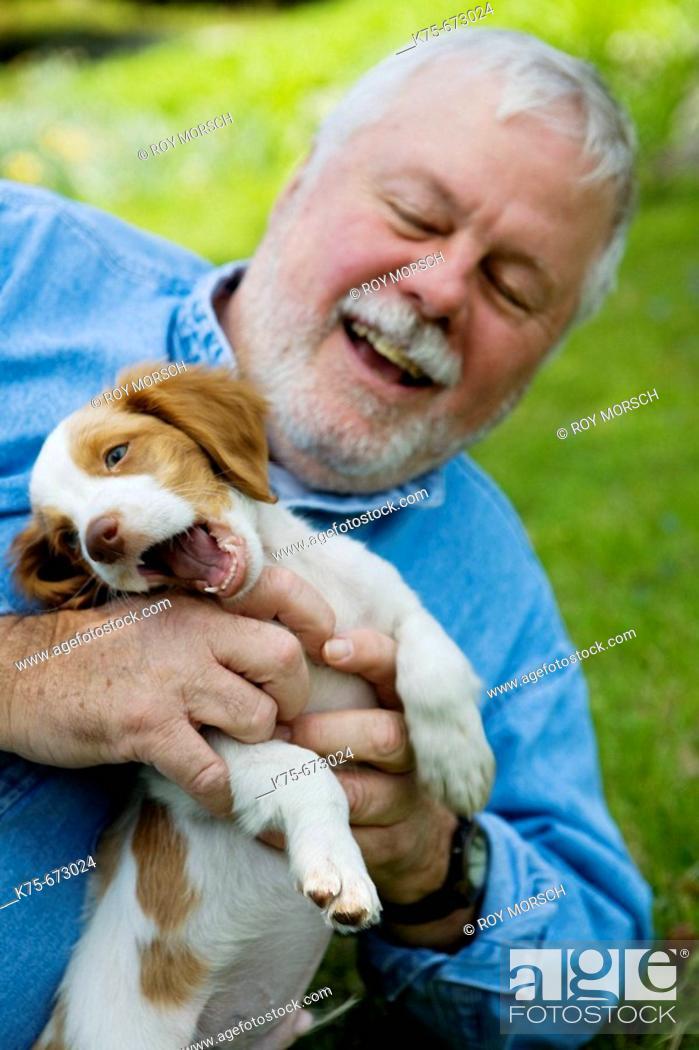 Stock Photo: Happy senior with his new puppy.
