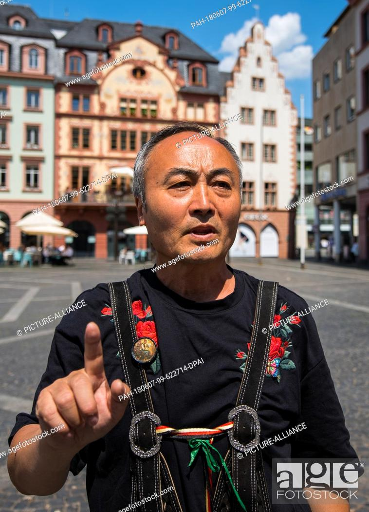 Stock Photo: 04 June 2018, Mainz, Germany: The Chinese Qing Wang sings on the Market square of the City's main street. The 59 year old educated singer and film director came.