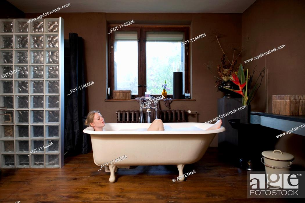 Stock Photo: A woman taking a bubble bath in a claw foot tub.