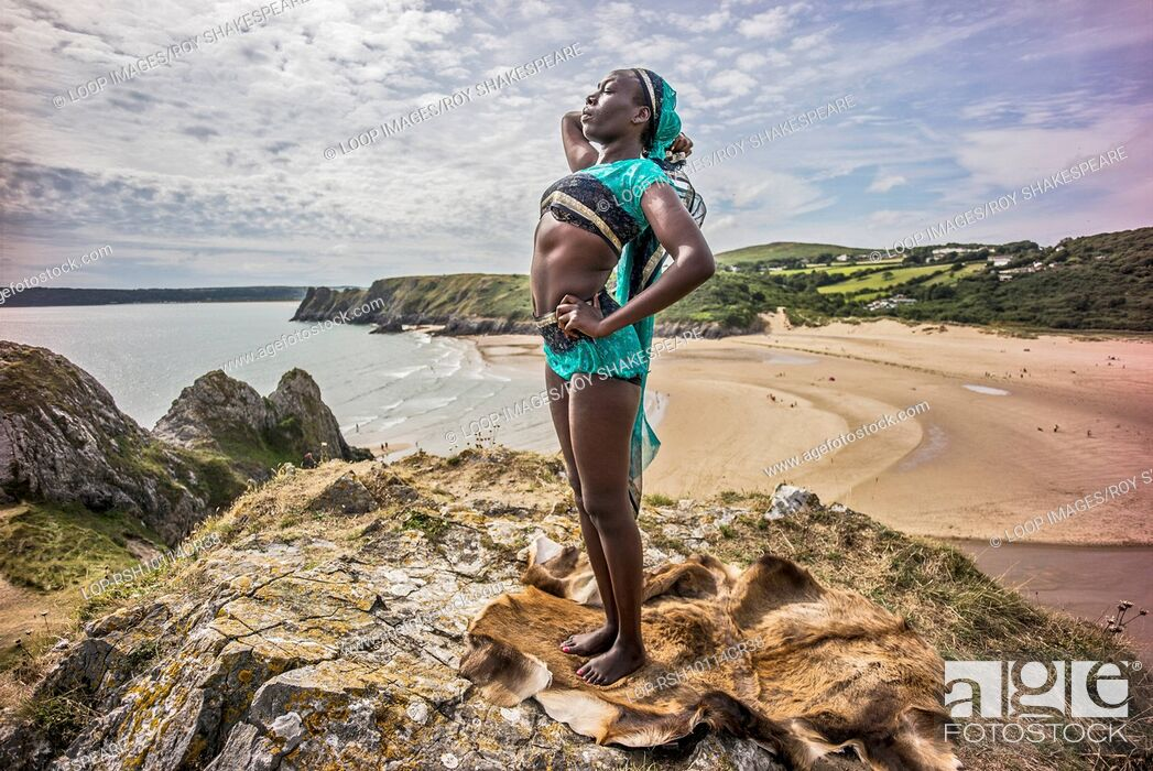 Imagen: An afro caribbean woman relaxing on hills overlooking Three Clffs Bay on the Gower.