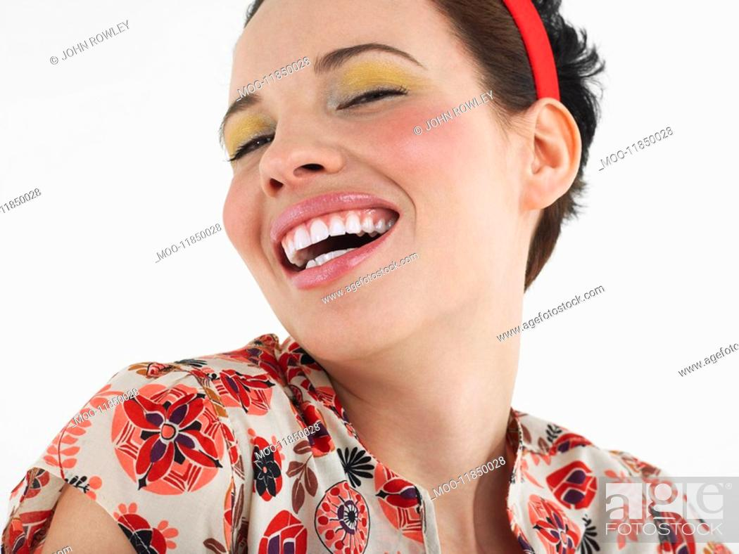 Stock Photo: Woman laughing head and shoulders in studio.
