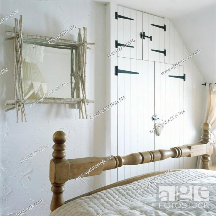 White twig framed mirror in white cottage bedroom with built in ...