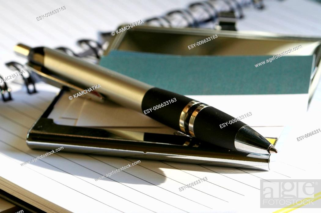 Stock Photo: pen lying on opened notebook.