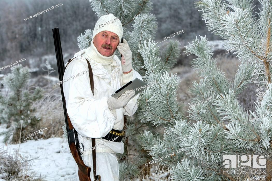 b2fb9bf32a4e2 Stock Photo - Winter hunting in white camouflage suit. Belgorod region.
