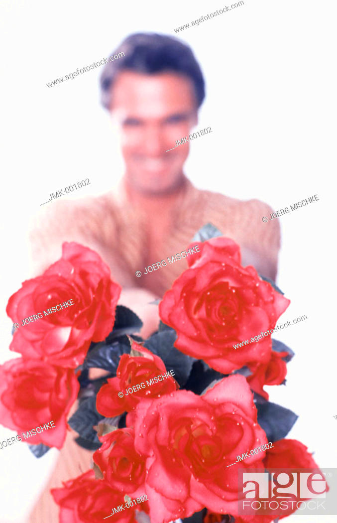 Stock Photo: Portrait of a young man, 20-25 25-30 30-35 years old, dark-haired, masculine and beautiful, offering a bouquet of red roses.