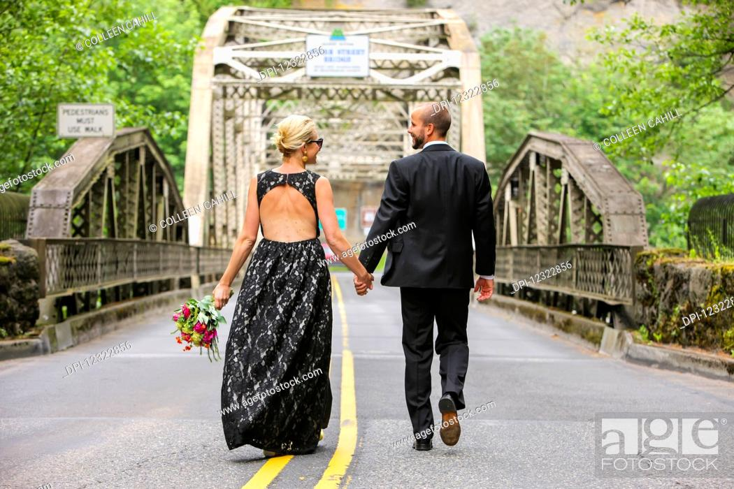 Stock Photo: A bride and groom holding hands and walking down a paved road; Oregon, United States of America.