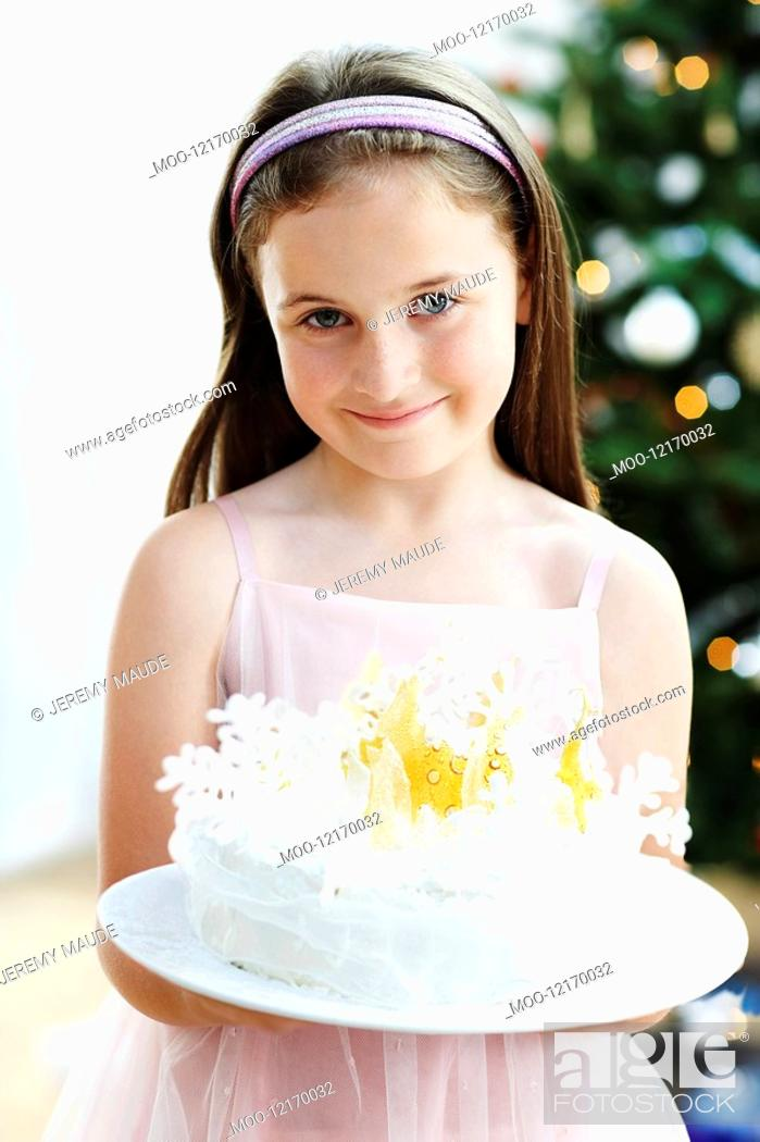 Stock Photo: Girl holding Snowflake-Decorated Cake in living room.