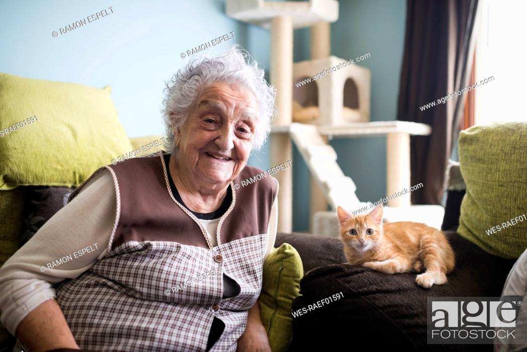Stock Photo: Portrait of happy woman and her cat sitting on couch in the living room.