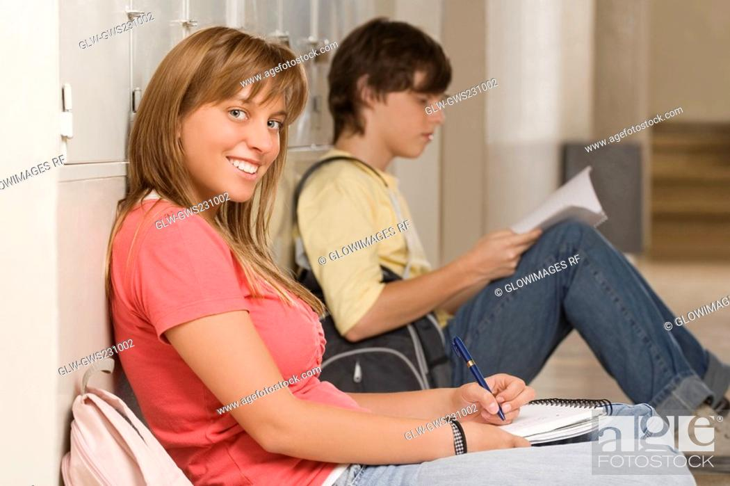 Stock Photo: Portrait of a teenage girl leaning against a wall and studying with a teenage boy beside her.