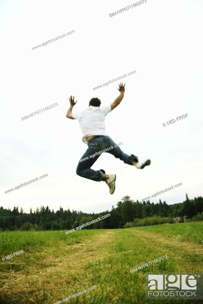 Stock Photo: Man jumping in field.