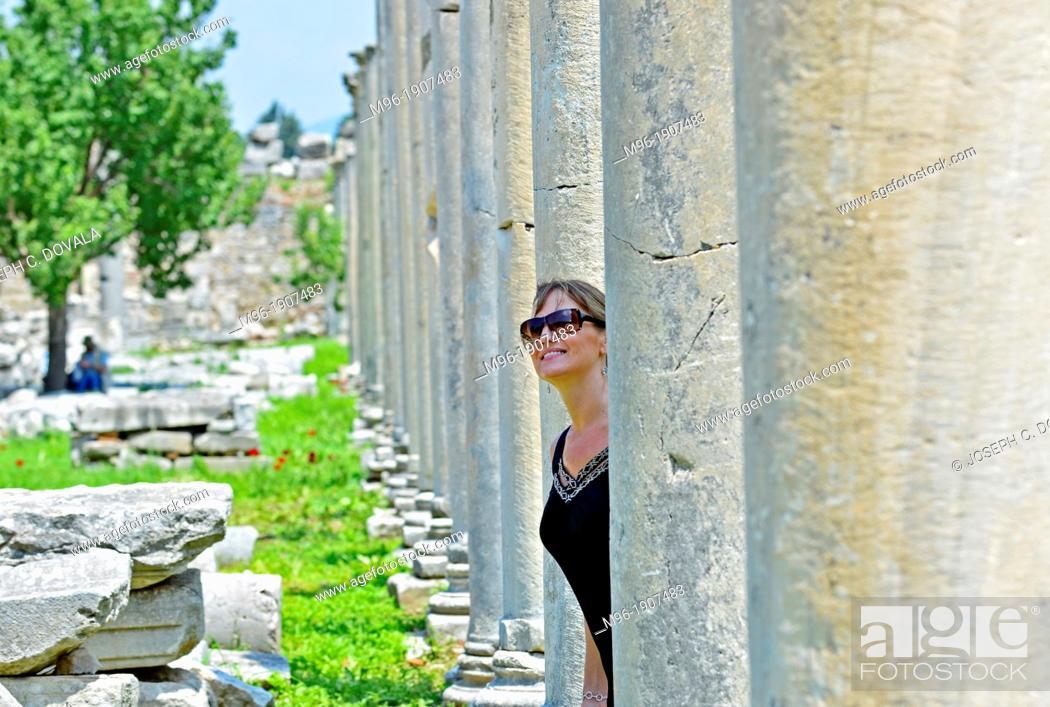 Stock Photo: Woman tourist looks out from marble pillars at Ephesus, Turkey.