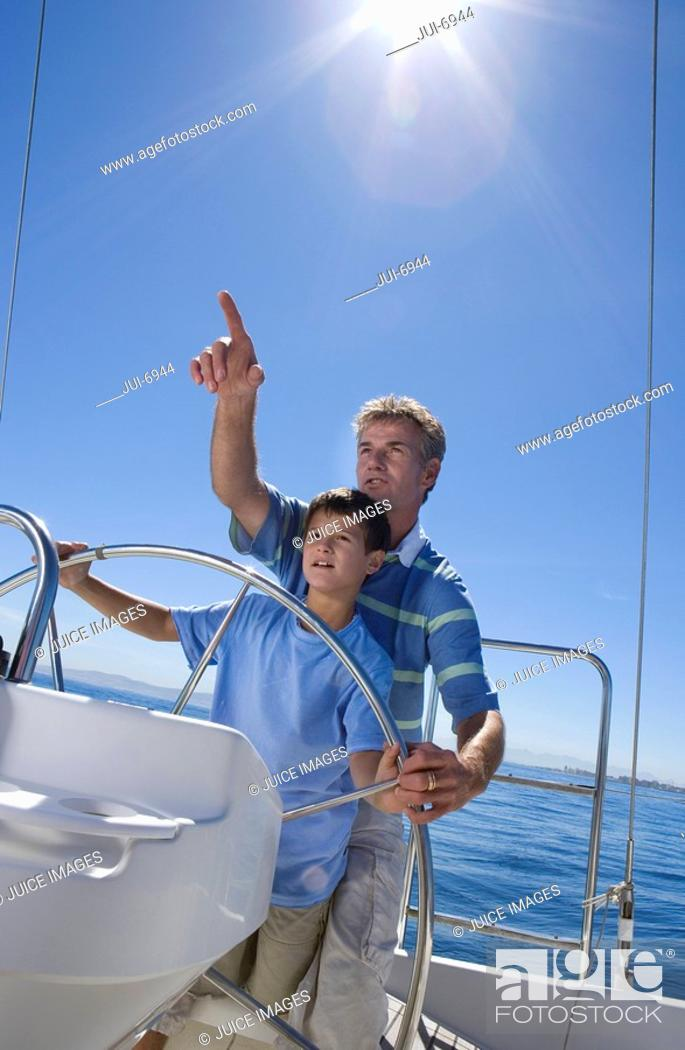 Stock Photo: Father and son 8-10 standing at helm of sailing boat out at sea, man pointing direction, boy steering lens flare, tilt.