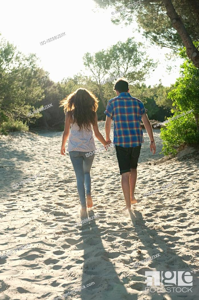 Stock Photo: Young couple walking across sand, rear view.