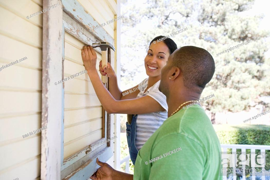 Photo de stock: Couple attaching frame to outside of house.
