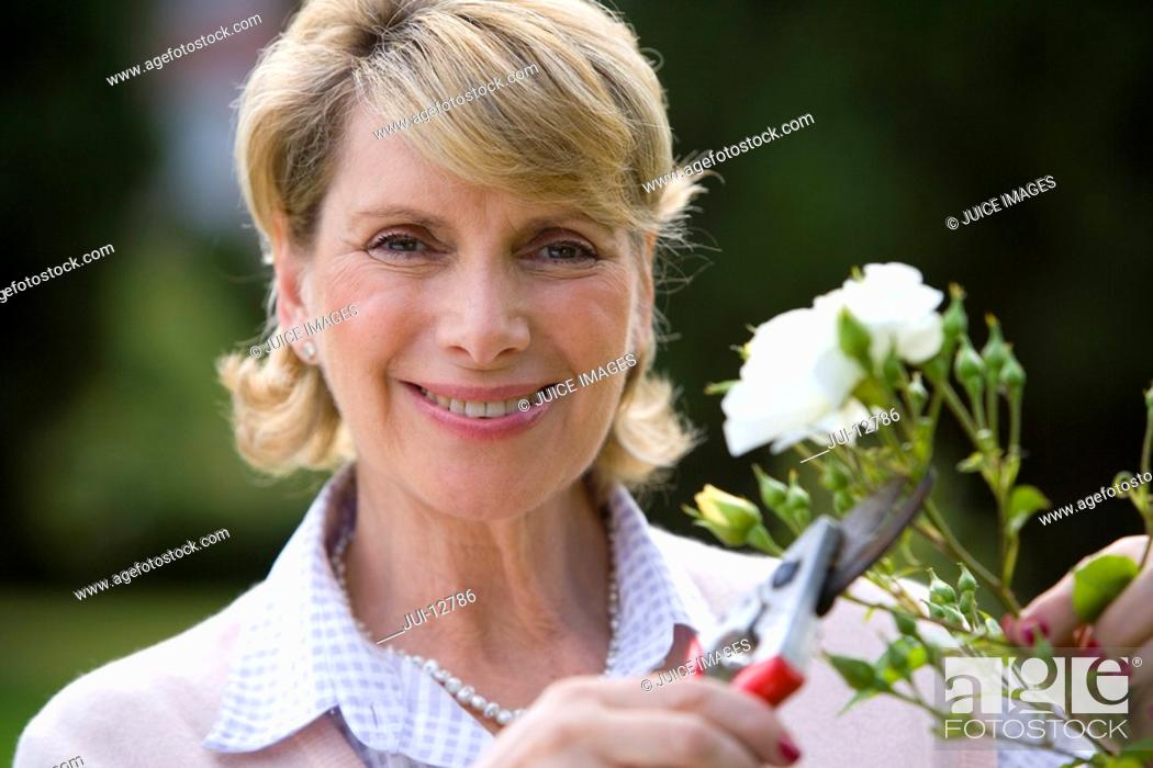 Stock Photo: Mature woman pruning bush with secateurs, smiling, portrait.