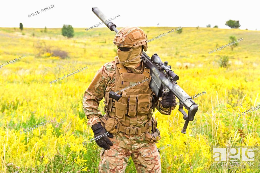 Imagen: Soldier in a special military uniform, with a helmet on his head and with a sniper rifle in the field.