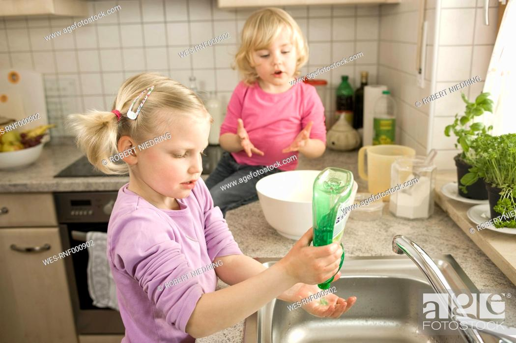 Stock Photo: Girl washing hands, sister sitting in background.