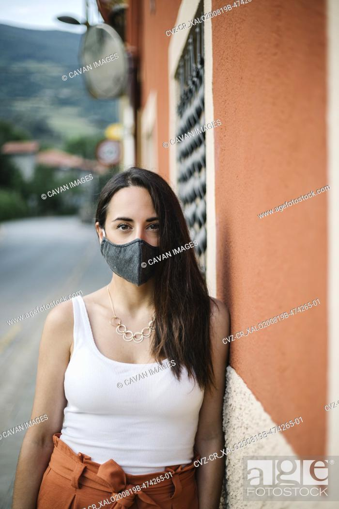 Stock Photo: Portrait of woman wearing mask in the street.
