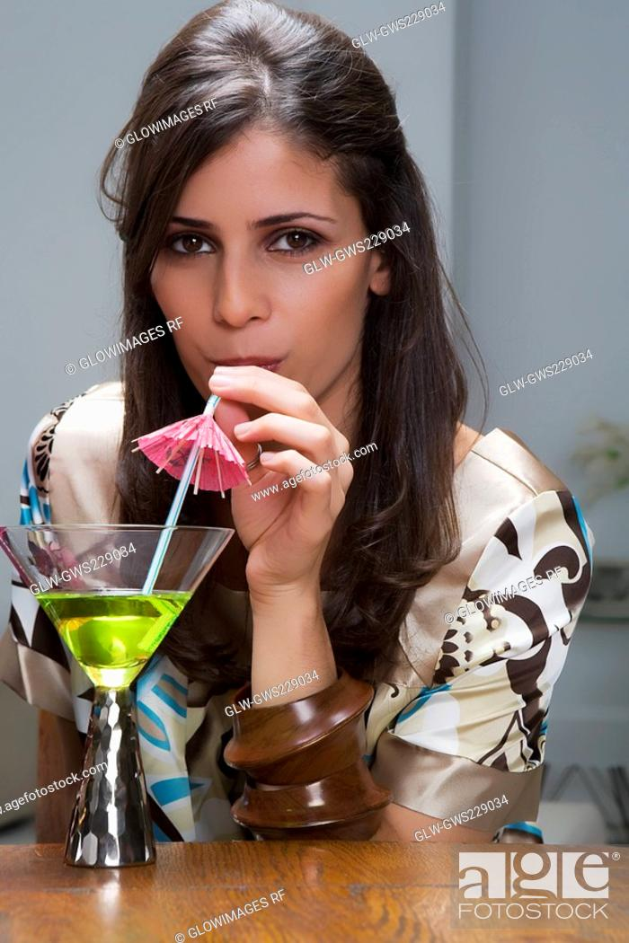 Stock Photo: Portrait of a young woman drinking cocktail.