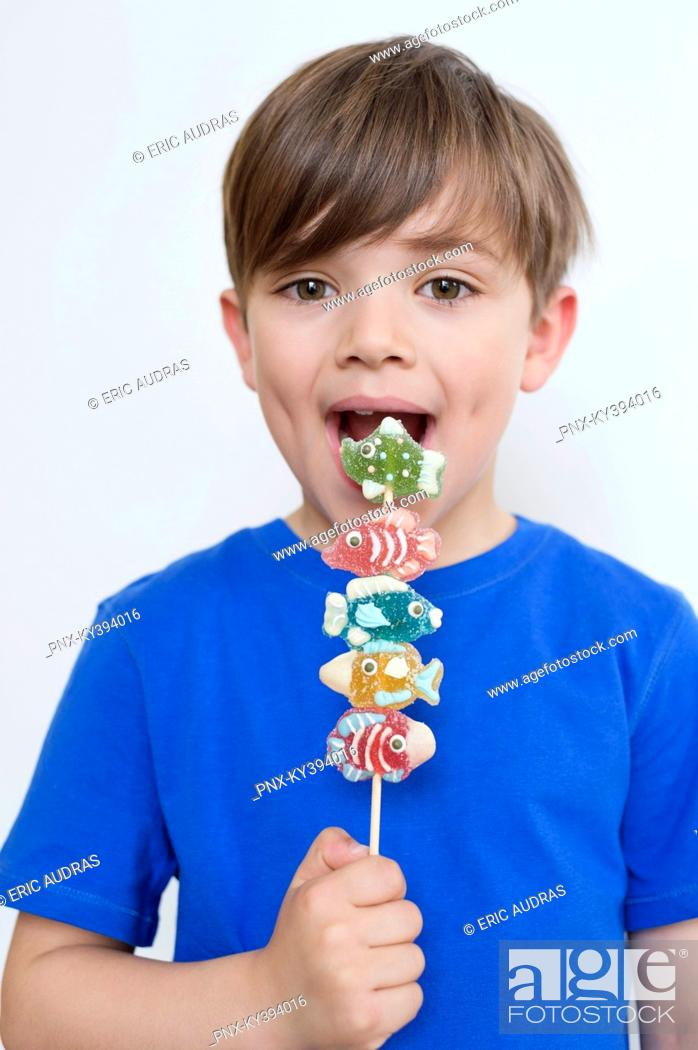 Stock Photo: Boy eating candies.