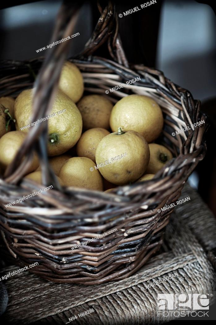 Stock Photo: Still life with lemons basket of bulrushes on the chair in the kitchen.
