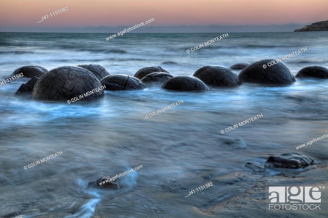 Stock Photo: Moeraki boulders at dusk, glow over Pacific Ocean, near Oamaru, Otago, New Zealand.