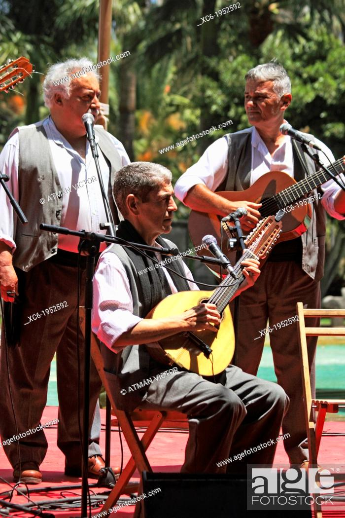 Stock Photo: two canarian guitarists standing and one seated playing folklore songs.