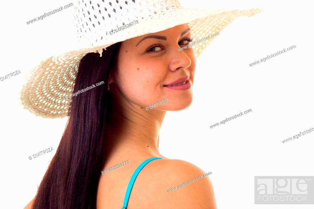 Stock Photo: Young pleasant woman with long dark hair in blue swimming suit and white hat on white background in studio.