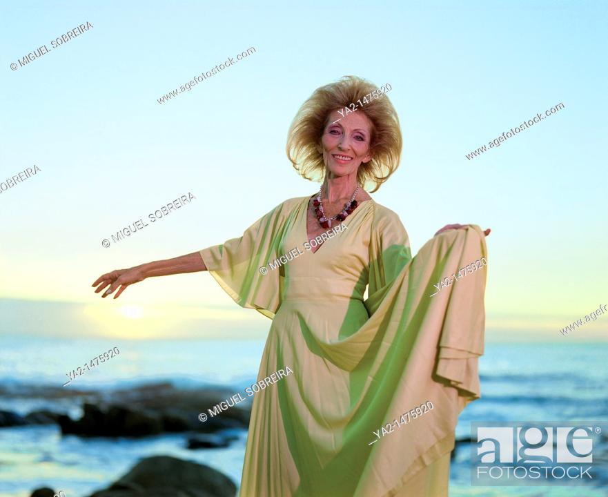 Stock Photo: Sophisticated Senior Woman 'dances' at seaside.