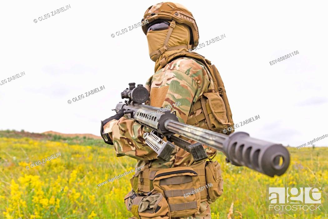 Imagen: Special forces soldier standing in the green field with sniper rifle.