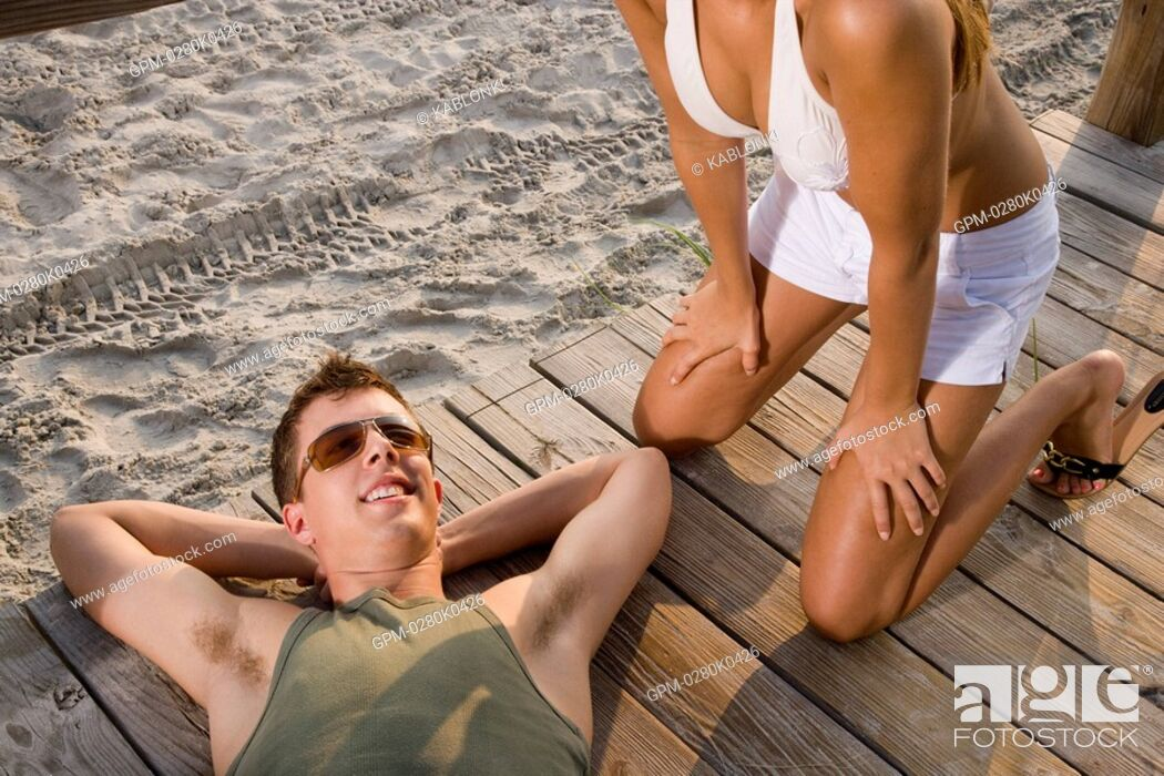 Imagen: Young man lying on wooden deck at beach, woman kneeling beside.
