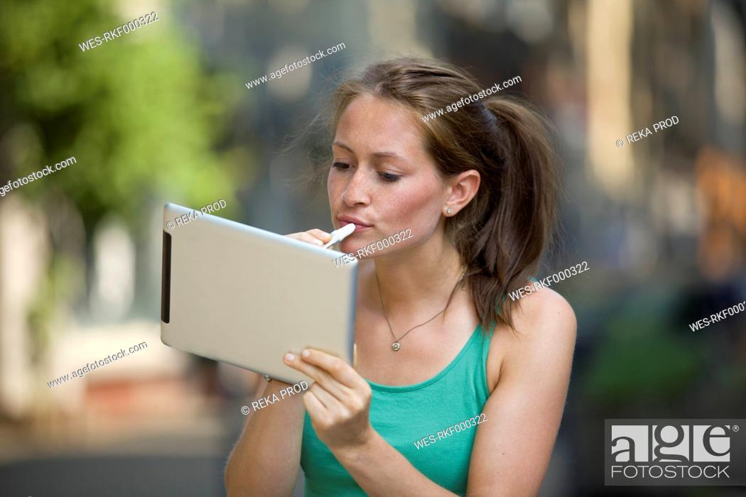 Stock Photo: Germany, North Rhine Westphalia, Cologne, Young woman using digital tablet as mirror.