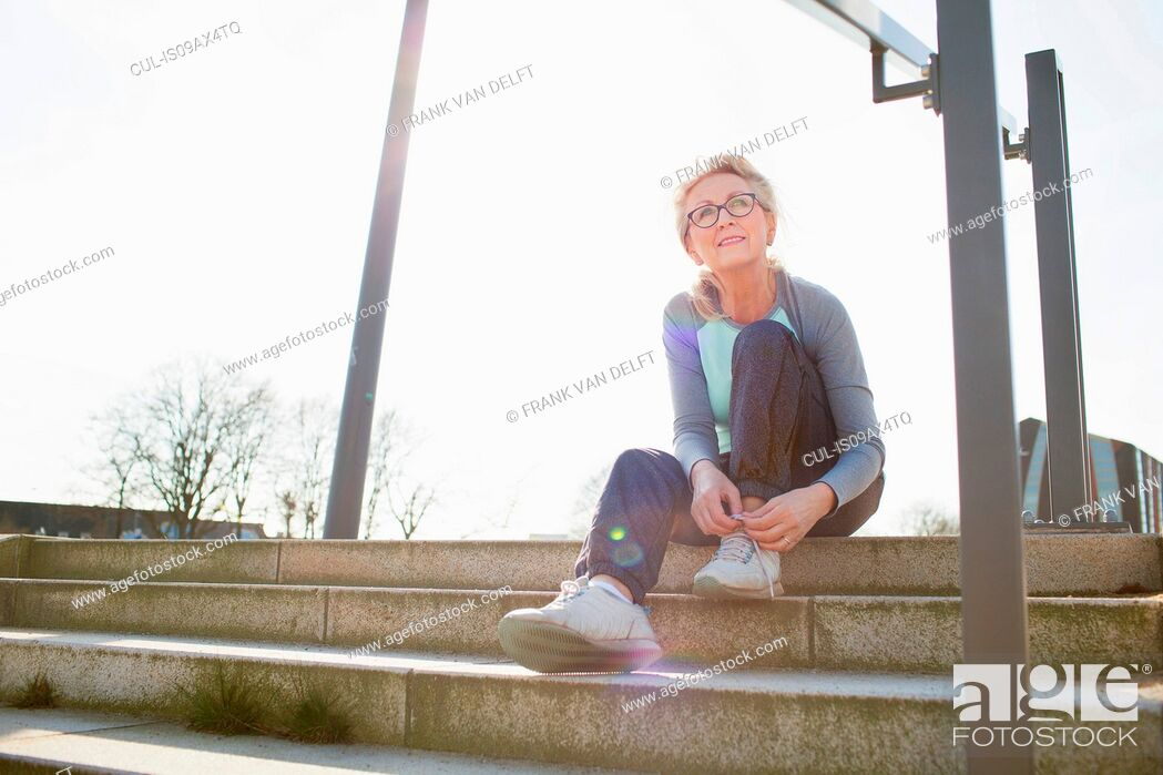 Stock Photo: Woman sitting on steps tying shoelace looking away.