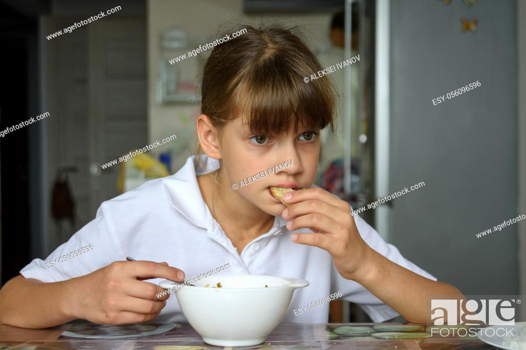 Stock Photo: Tired hungry schoolgirl eating soup at the table in the kitchen.