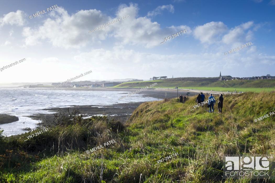 Stock Photo: People walking along the coastal path of Seaton Cliffs towards the Victoria Park beachfront in Arbroath, Scotland.