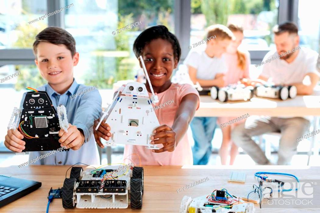 Stock Photo: Talented teens. Cheerful smiling children showing their robot models of cosmic warriors to the camera while their teacher explaining new material to their.