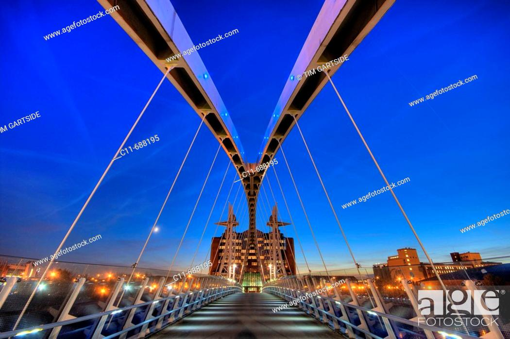 Stock Photo: lowry pedestrian suspension footbridge and office block night dusk evening salford quays manchester england uk europe.