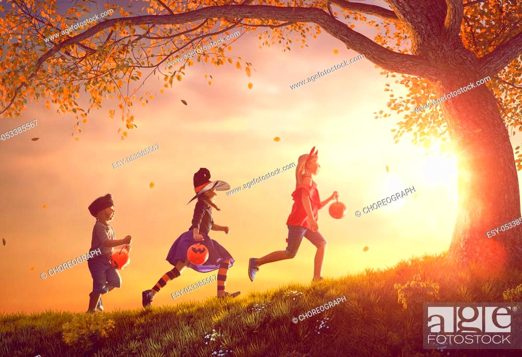 Stock Photo: Happy brother and two sisters at Halloween. Funny kids in carnival costumes outdoors. Cheerful children and pumpkins on sunset background.