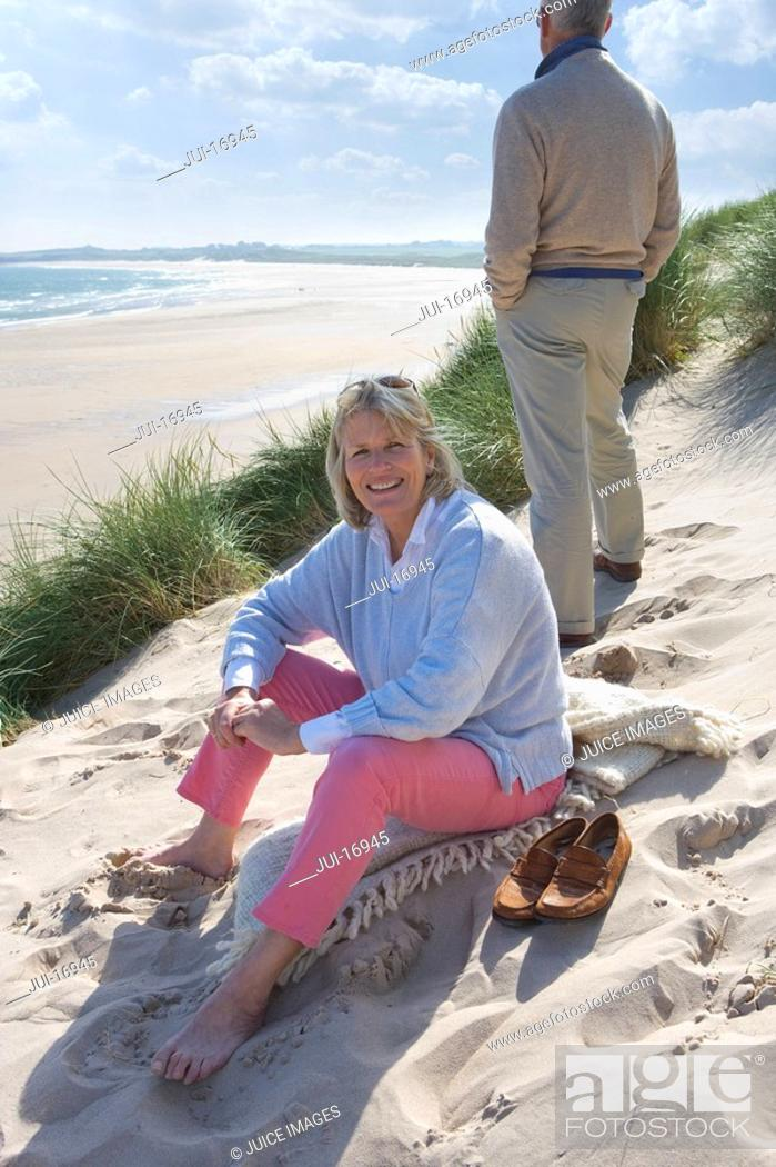 Stock Photo: Mature woman sitting on beach, man standing in background.